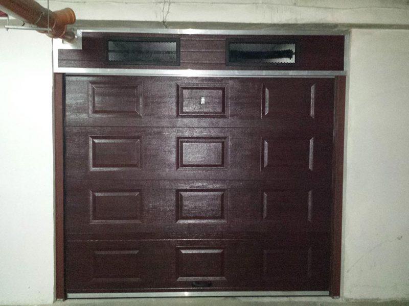 София - Секционна гаражна врата с мотор. Цвят махагон, монтирана върху метална рамка и допълнителен панел с отвори за проветрение.