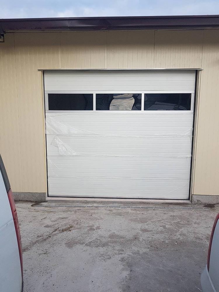 Първомай - Гаражна секционна врата с един остъклен панел (full vision) и вградена пешеходна врата. Цвят-бял(Ral-9010). 001