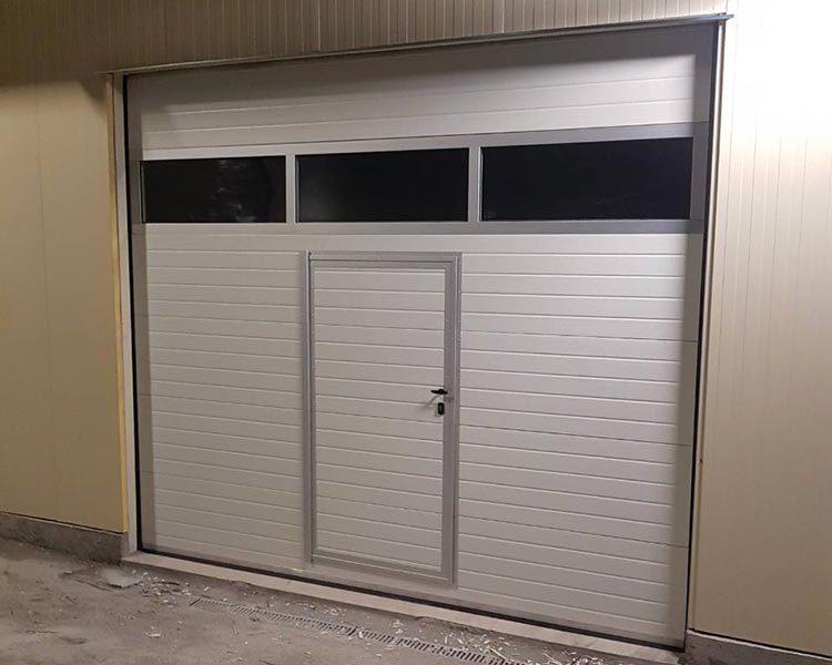 Първомай - Гаражна секционна врата с един остъклен панел (full vision) и вградена пешеходна врата. Цвят-бял(Ral-9010). 002