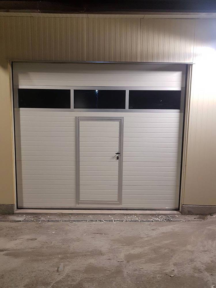 Първомай - Гаражна секционна врата с един остъклен панел (full vision) и вградена пешеходна врата. Цвят-бял(Ral-9010). 003