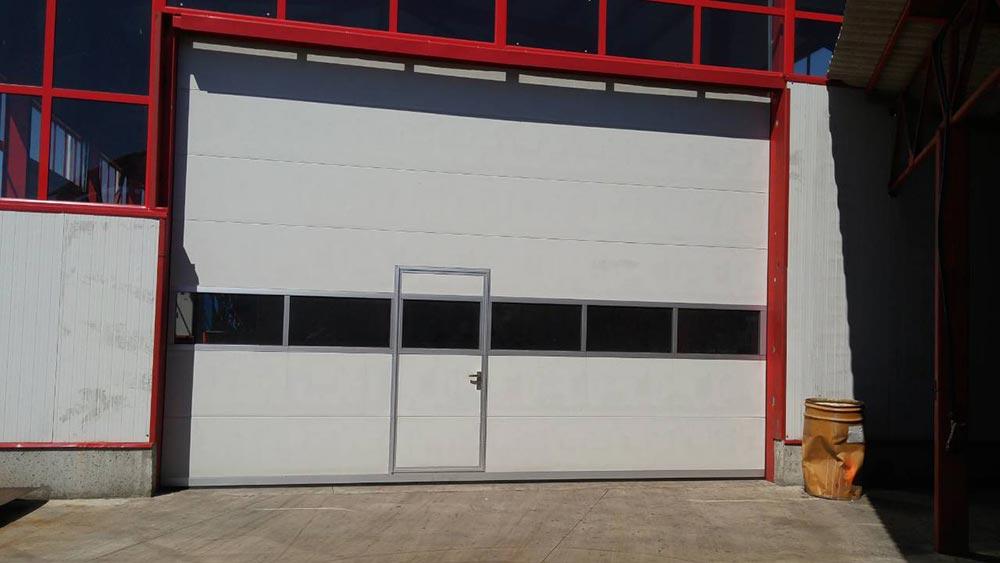 Стара Загора - Индустриална секционна врата с един остъклен панел и вградена проходна врата. Задвижване с редуктор 001