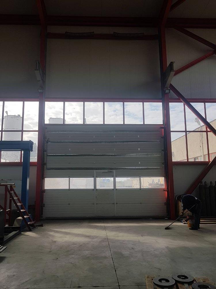 Стара Загора - Индустриална секционна врата с един остъклен панел и вградена проходна врата. Задвижване с редуктор 002