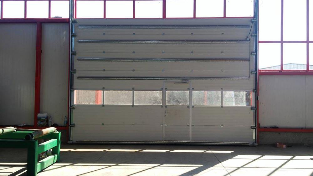 Стара Загора - Индустриална секционна врата с един остъклен панел и вградена проходна врата. Задвижване с редуктор 003