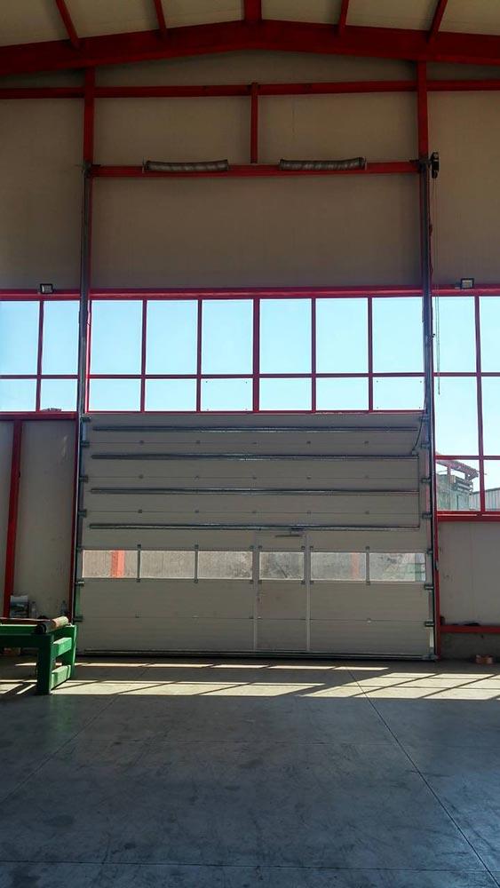 Стара Загора - Индустриална секционна врата с един остъклен панел и вградена проходна врата. Задвижване с редуктор 004