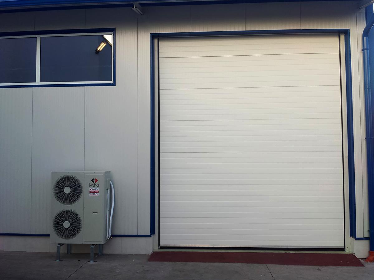 Първомай - Индустриални секционни врати в едната от които е вградена проходна врата_001
