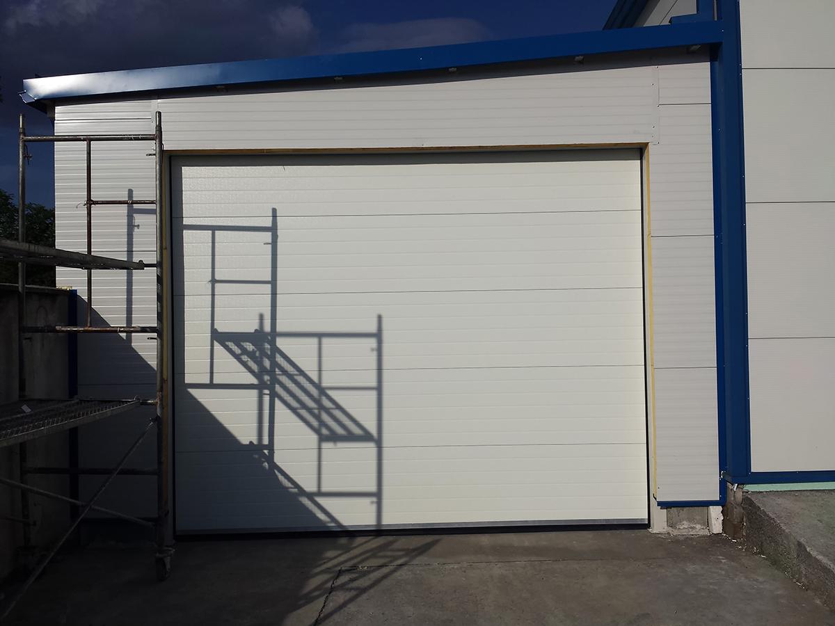 Първомай - Индустриални секционни врати в едната от които е вградена проходна врата_002