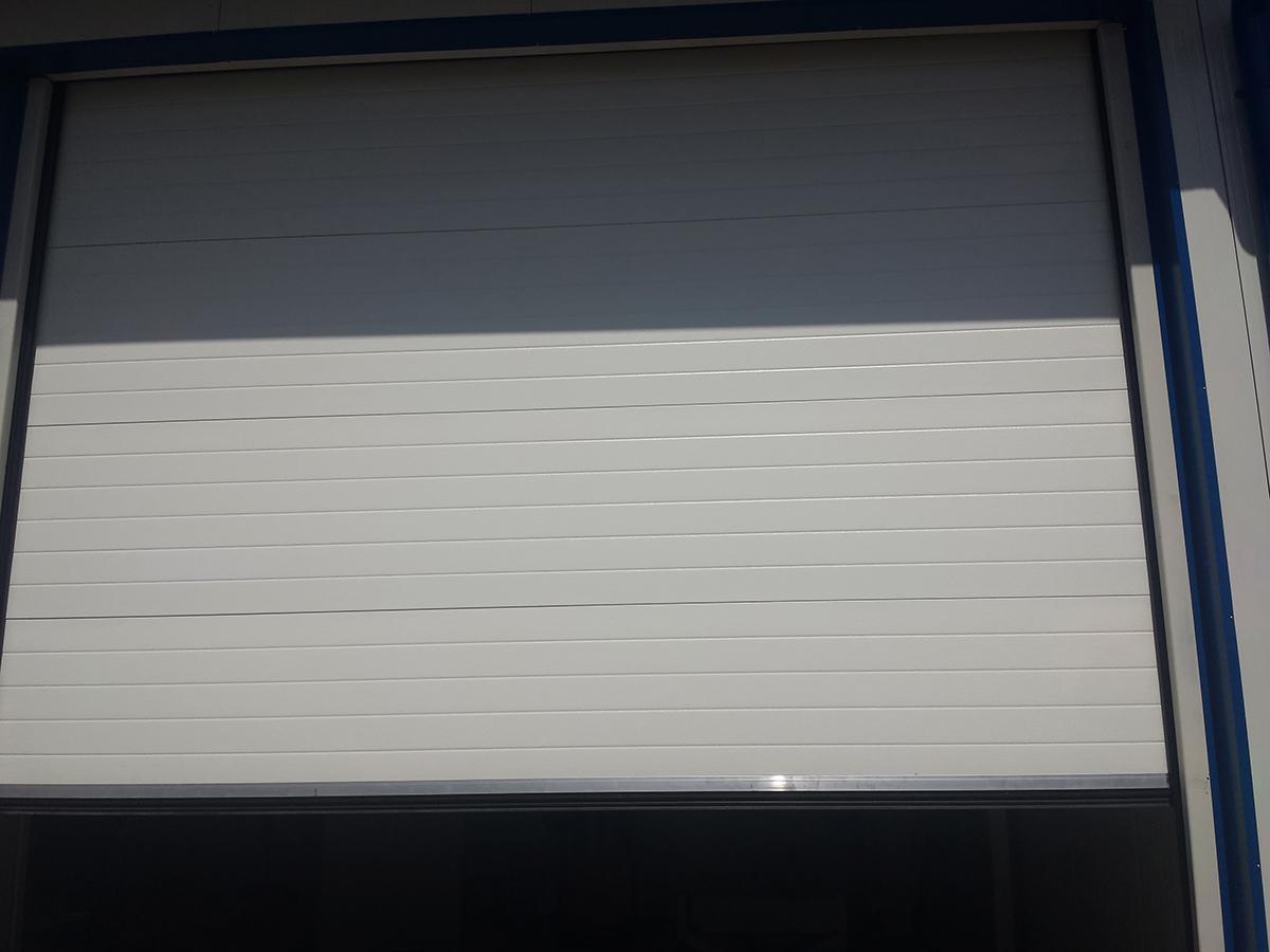 Първомай - Индустриални секционни врати в едната от които е вградена проходна врата_004