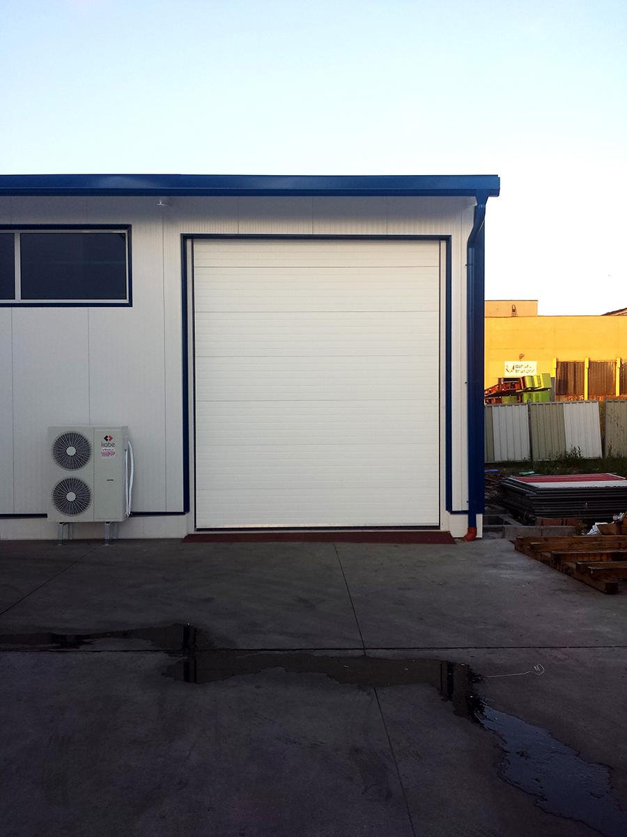 Първомай - Индустриални секционни врати в едната от които е вградена проходна врата_009