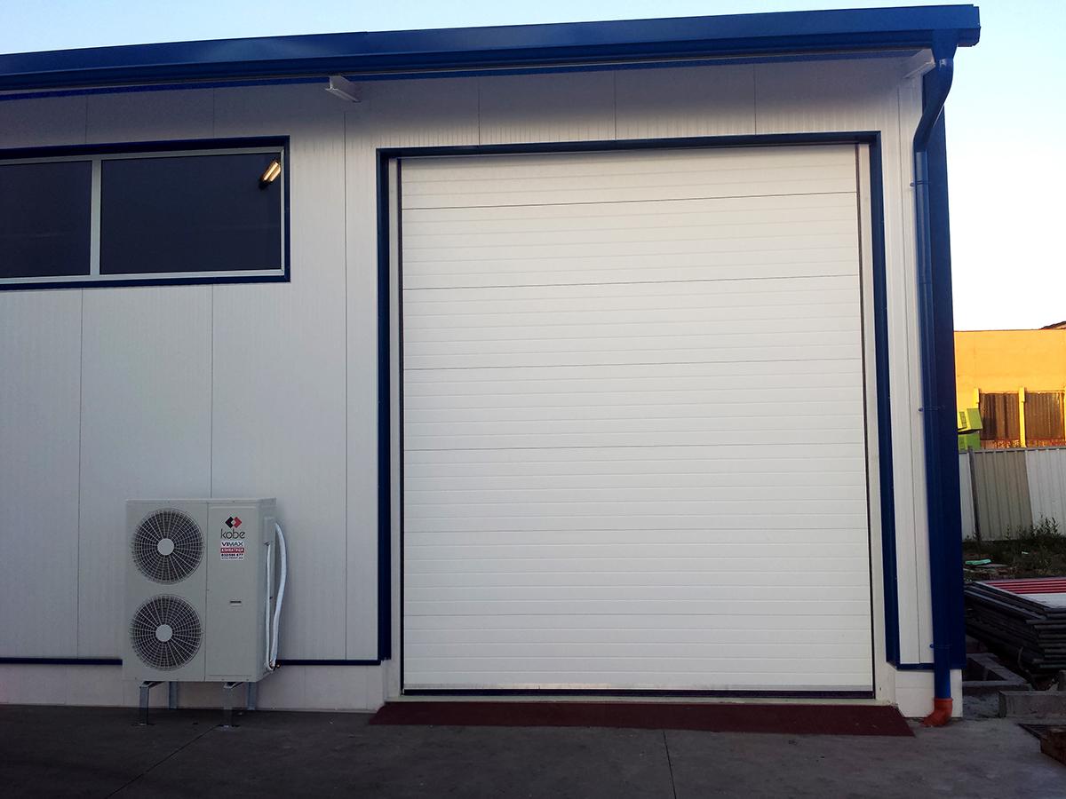 Първомай - Индустриални секционни врати в едната от които е вградена проходна врата_011