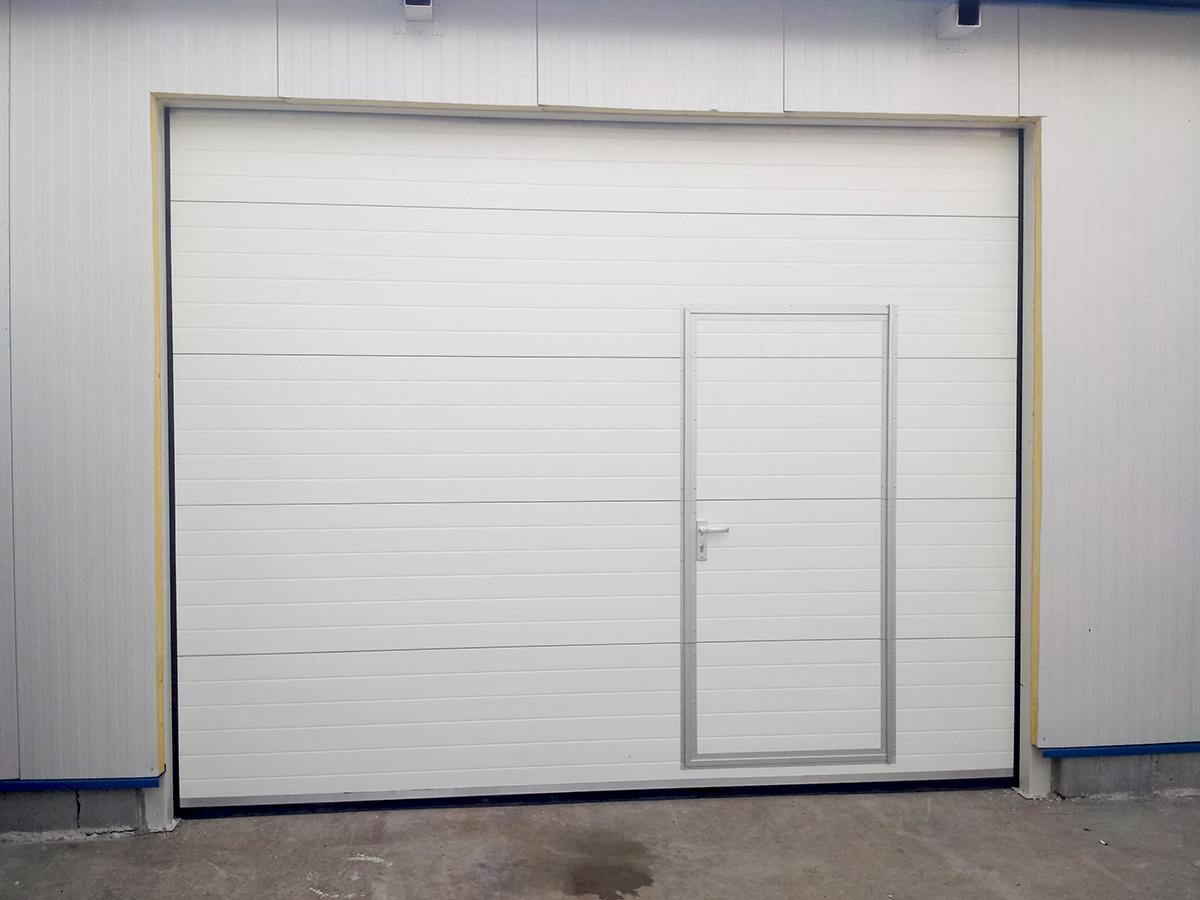 Първомай - Индустриални секционни врати в едната от които е вградена проходна врата_014