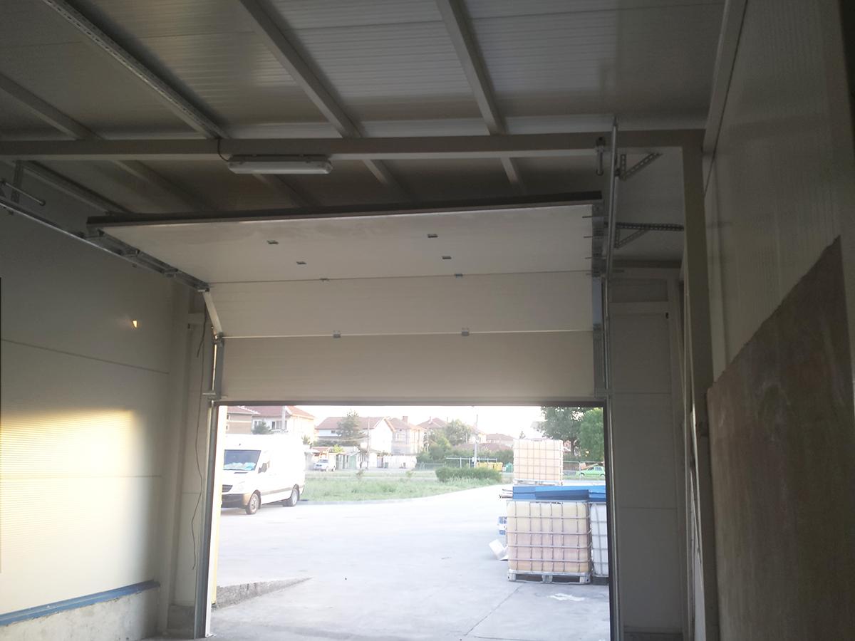 Първомай - Индустриални секционни врати в едната от които е вградена проходна врата_017