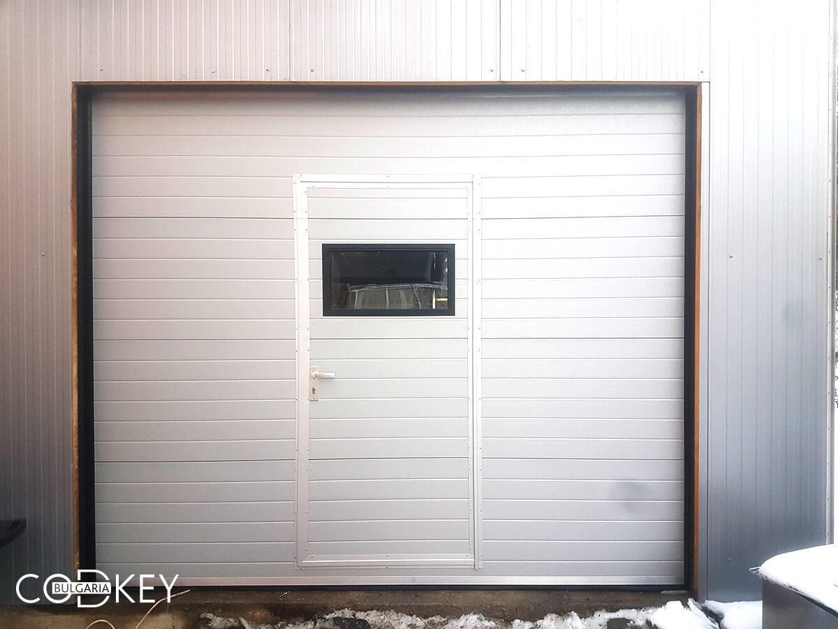 Гаражна секционна врата с вградена в нея проходна врата и един декоративен прозорец_001