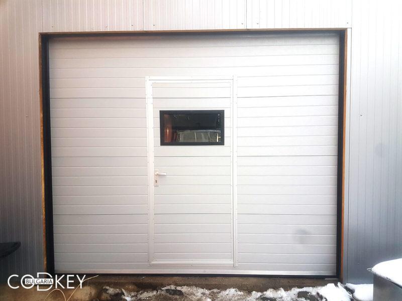 Гаражна секционна врата с вградена в нея проходна врата и един декоративен прозорец_002