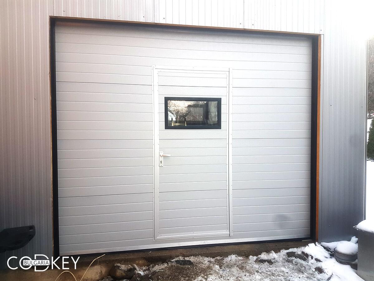 Гаражна секционна врата с вградена в нея проходна врата и един декоративен прозорец_003