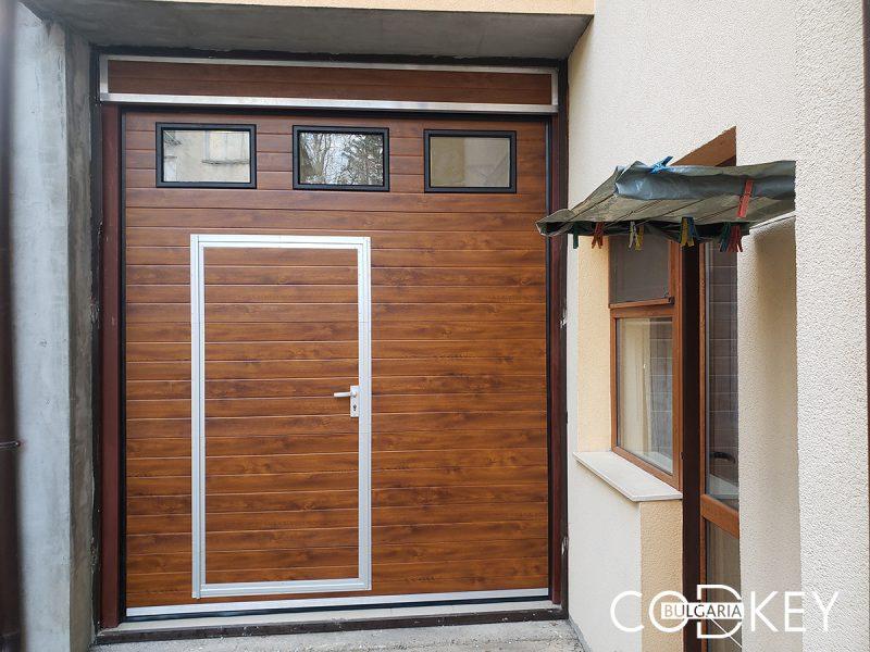 Гаражна секционна врата с вградена пешеходна и един ред декоративни прозорци в град Монтана 001